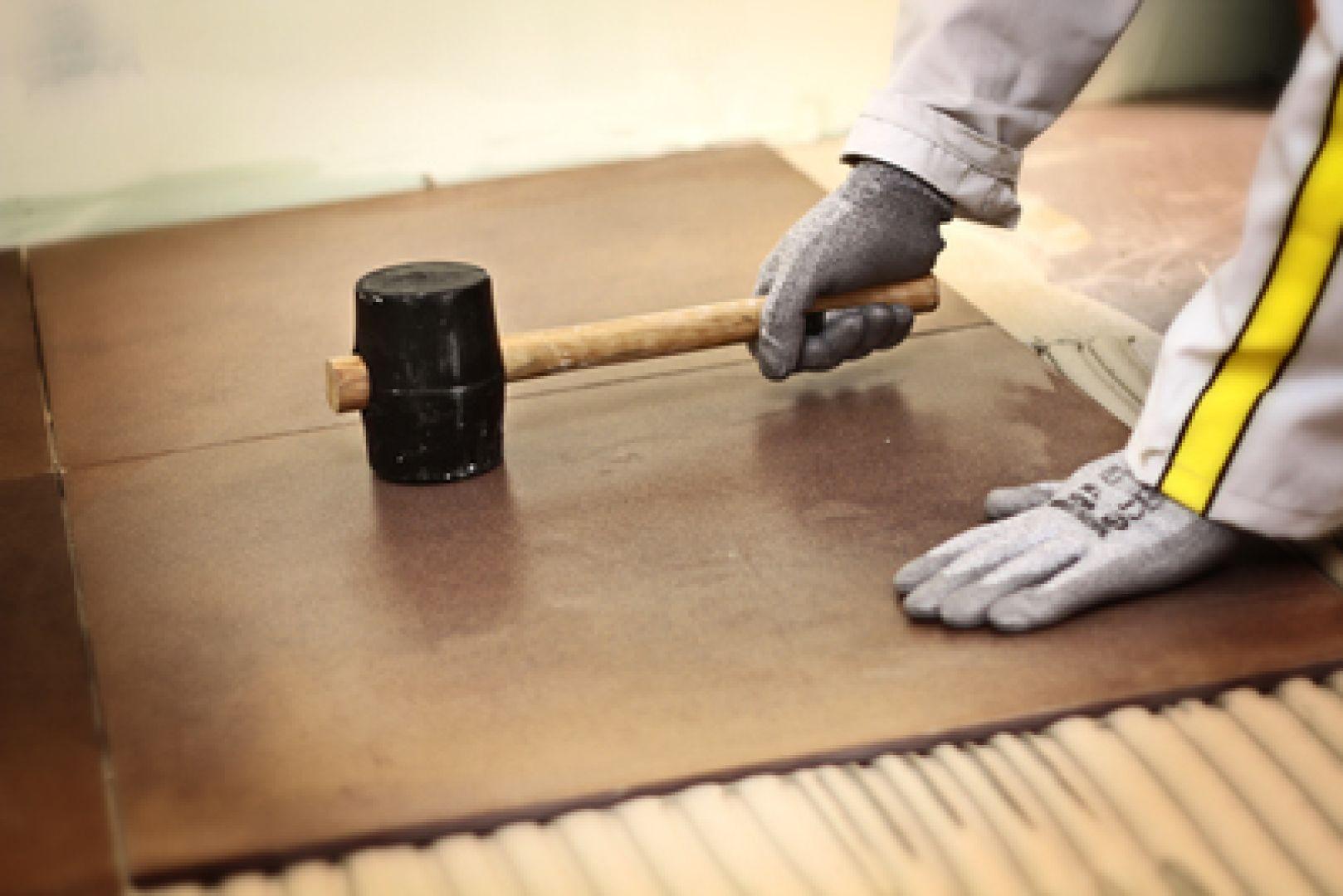dùng búa chuyên dụng ốp gạch lên trên lớp keo dán gạch